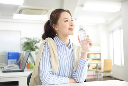オフィスで水を飲む女性