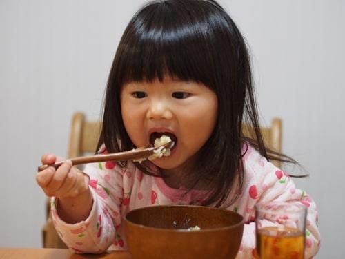 おかゆを食べる女の子