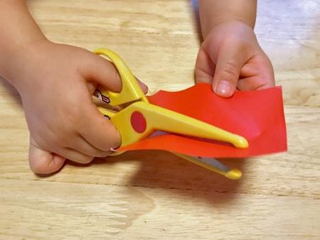 はさみで工作をする三歳の子供のイメージ画像